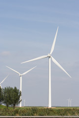 White wind turbine standing on open plain.