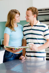 A young attractive couple at home in the kitchen