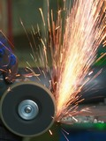 Yellow hot sparks at grinding steel material.. poster