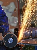 Yellow hot sparks at grinding steel material poster