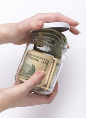 hands closing glass jar with money