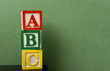 ABC blocks in front of a green chalkboard with copy space poster