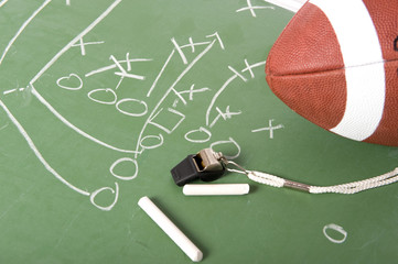 A diagram of a football play on a chalkboard with a football,