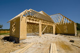 A new home being built with wood, trusses, supports poster