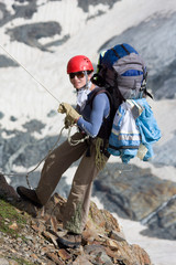 Climber girl going down on rope in mountains