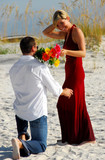 Man down on one knee offering bouquet to woman poster