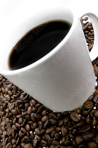 Close up of coffee beans and cup over white background