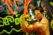 Bodybuilder flexing bicep against graffiti