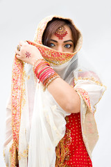 Elegant Bengali bride with veil in front of mouth, isolated