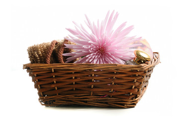 Basket with natural spa elements and pink flower isolated