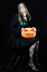 Sexy vampire girl with halloween pumpkin on black background