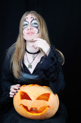 Portrait of pretty vampire girl with halloween pumpkin