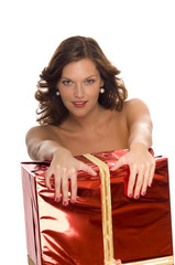 Beautiful naked model behind a big Christmas gift