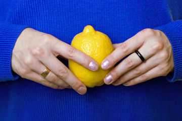 hands of a girl carrying a lemon