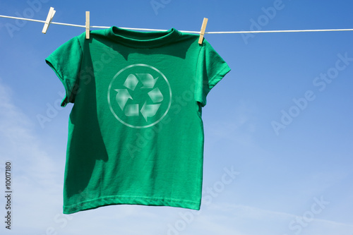 canvas print picture A green t-shirt hanging on a clothesline with the recycle symbol