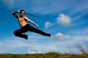 Young handsome man with samurai sword jumping