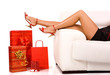 Attractive woman lie on couch  with colorful shopping bag