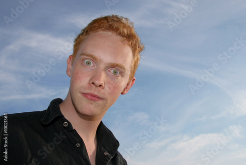 Wide-eyed young man against blue sky