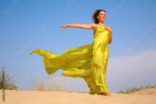Young girl on sand in yellow fabric shawl