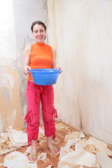 Girl with basin of water makes room renovations