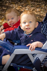 Twin brothers with red hair sitting in stroller outside