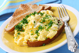 Scrambled eggs garnished with parsley, with sourdough toast. poster