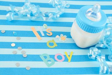 a blue baby bottle with milk and celebratory it's a boy text