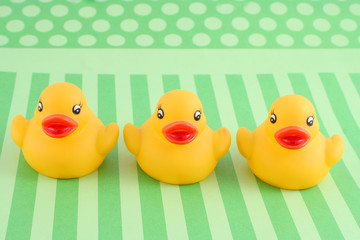 three child's rubber duck on top of green  striped background