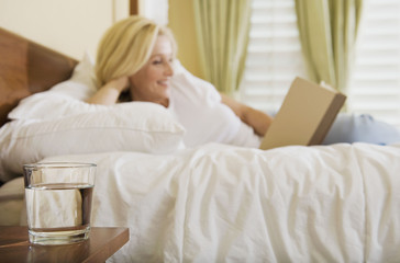 Relaxed woman reclining in bed enjoying reading a book with glass of water in foreground