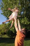 father tossing daughter in the air at the park
