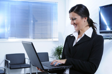 Businesswomanand smile; to make use of laptop pc