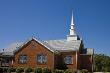 An old small  brick baptist church and blue sky
