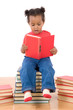 Adorable african baby reading sitting on a pile of books