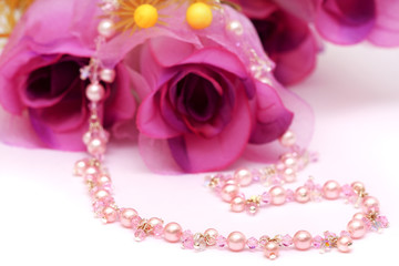 A pink color beads necklace put with flower.