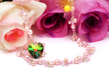A heart shape bead and pink necklace put with flowers.