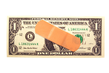 A band-aid on a US one dollar bill on white