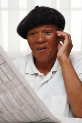 Ethnic woman reading the paper and looking surprised