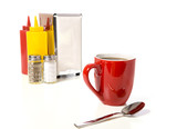 A cafe or coffee shop tabletop setup with a yellow cup poster