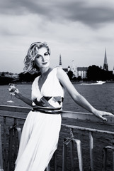 Beautiful blond girl drinks champagne near the river