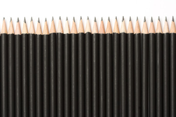 Black pencils lined up on white background.