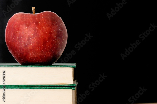 A red apple red on a green book on a black background