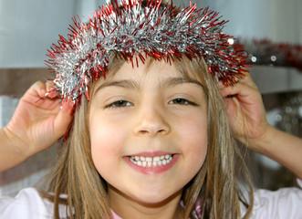 fillette coifffant sa couronne en guirlande de Noël