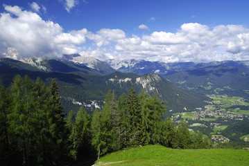 View at alpine mountain peaks with forests  and cloudy sky