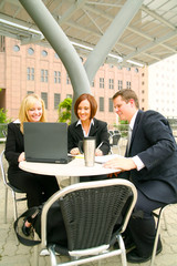 three businesspeople having a group meeting outdoor