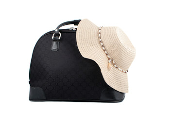 small suitcase with straw beach hat  ready for a summer