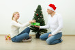 The man gives a gift to the woman against a Christmas pine