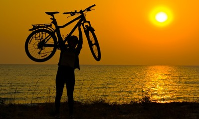 Mountain biker girl silhouette in sunrise.