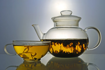 Glass teapot and cup with green tea on grey background