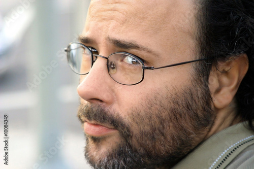 Portrait of a serious bearded man with glasses