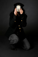 Retro style female photographer with vintage camera and flash